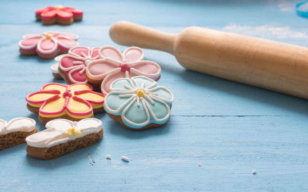 Flower shaped gingerbread cookies and rolling pin on a blue wooden table.