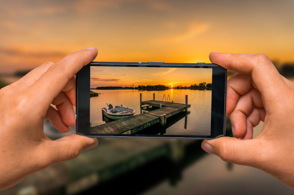 Woman hands with mobile cell phone to take a photo of sunset over lake in the Netherlands
