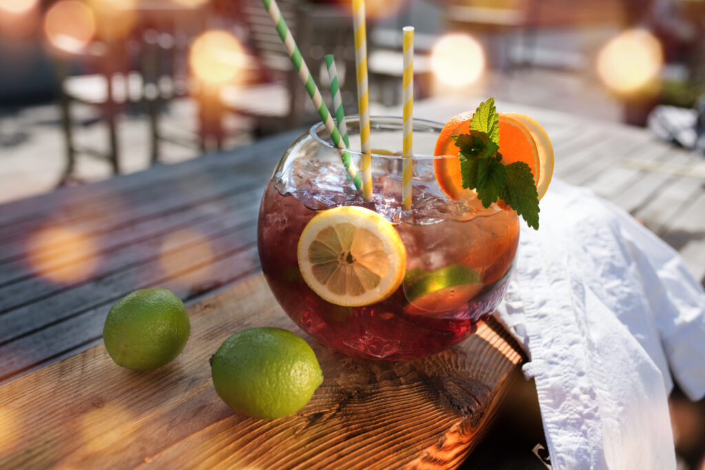 Sangria or punch with fruit on a wooden table in a restaurant and bokeh