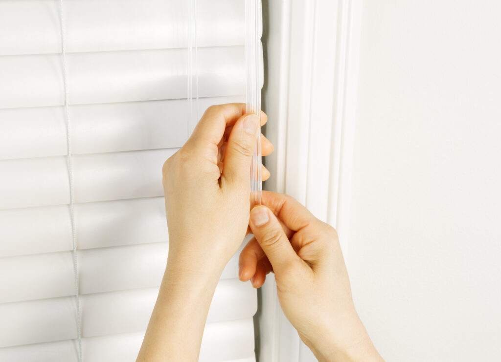 Photo of female hands using wand to close windows blinds